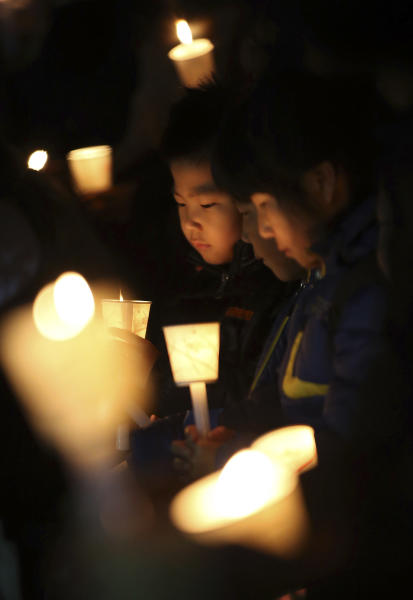 Kindergartens hold candles as they pray for safe return of passengers of the sunken ferry Sewol, in Ansan, South Korea, Sunrday, April 20, 2014. After more than three days of frustration and failure, divers on Sunday finally found a way into the submerged ferry off South Korea's southern shore, discovering more than a dozen bodies inside the ship and pushing the confirmed death toll to over four dozens, officials said. (AP Photo/Yonhap) KOREA OUT