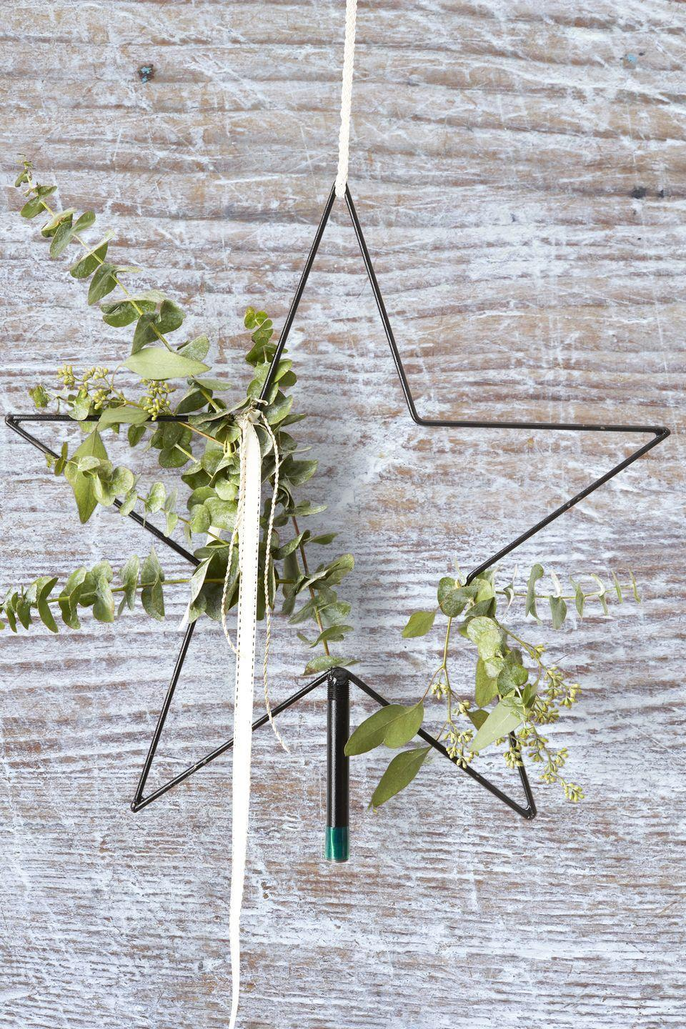 "<p>Spruce up a wire tree topper with eucalyptus, green sprigs, and neutral ribbon for an instant farmhouse feel. </p><p><strong>RELATED: </strong><a href=""https://www.goodhousekeeping.com/holidays/christmas-ideas/g2721/christmas-tree-toppers/"" rel=""nofollow noopener"" target=""_blank"" data-ylk=""slk:Unique Christmas Tree Toppers to Match Any Holiday Theme"" class=""link rapid-noclick-resp"">Unique Christmas Tree Toppers to Match Any Holiday Theme</a></p>"