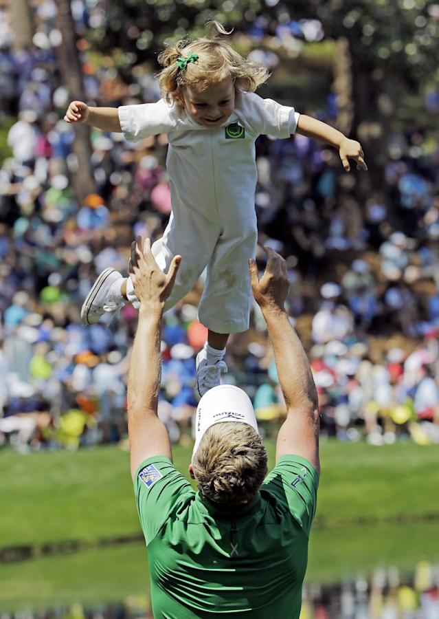 Luke Donald, of England, throws his youngest daughter Sophia in the air during the par three competition at the Masters golf tournament Wednesday, April 9, 2014, in Augusta, Ga. (AP Photo/David J. Phillip)