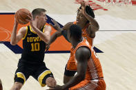 Iowa's guard Joe Wieskamp (10) looks to pass as Illinois guard Ayo Dosunmu and center Kofi Cockburn defend in the first half of an NCAA college basketball game Friday, Jan. 29, 2021, in Champaign, Ill. (AP Photo/Holly Hart)