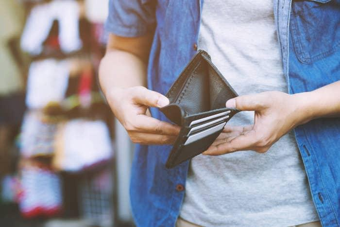 Person opening an empty wallet