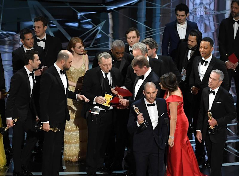 """""""La La Land"""" producer Fred Berger (R) speaks at the microphone as production staff and representatives from PricewaterhouseCoopers, Martha L. Ruiz (red dress) and Brian Cullinan, consult behind him at the Oscars"""