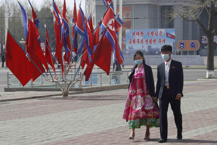 FILE - In this April 15, 2021, file photo, a man and a woman wearing face masks walk along a street on the Day of the Sun, the birthday of late leader Kim Il Sung, in Pyongyang, North Korea. After saying for months that it kept the coronavirus completely at bay, North Korea on Wednesday, June 30, 2021, came its closest to admitting that its anti-virus campaign has been less than perfect. (AP Photo/Jon Chol Jin, File)