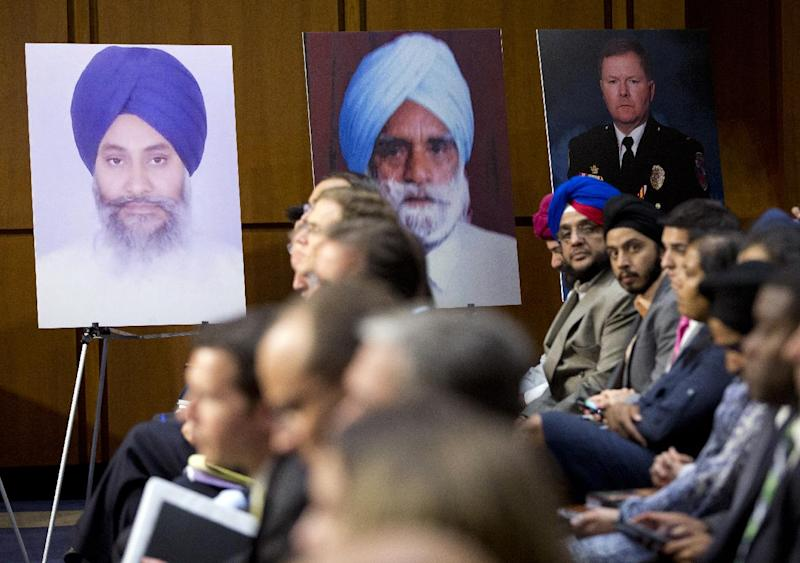 Photographs of the victims of the attack that left six Sikh worshipers dead in Oak Creek, Wis., line the walls during a hearing on Capitol Hill on Wednesday, Sept. 19, 2012 in Washington.  (AP Photo/ Evan Vucci)