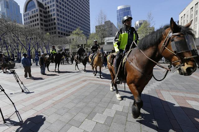 Mounted Seattle police officers ride through Westlake Center on a day of May Day demonstrations and protests, Wednesday, May 1, 2013 in downtown Seattle. (AP Photo/Ted S. Warren)