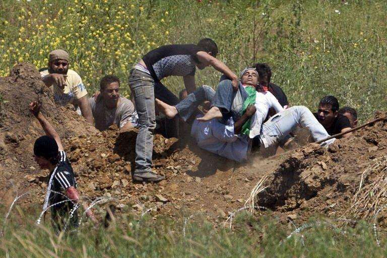 Demonstrators prepare to evacuate a wounded fellow protestor who was hit by Israeli fire while trying to cut through a line of barbed wire and head into the Israeli-annexed Golan Heights. Israeli troops opened fire on Sunday as protesters from Syria stormed a ceasefire line in the occupied Golan Heights, with Damascus saying 23 demonstrators were killed