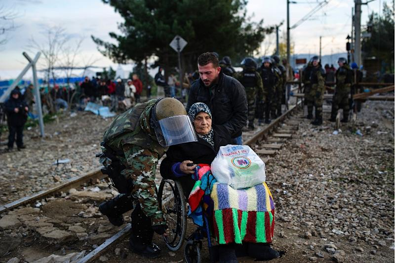 A Macedonian soldier helps an elderly woman in a wheelchair after crossing the Greek-Macedonia border near Gevgelija on November 28, 2015 (AFP Photo/Robert Atanasovski)