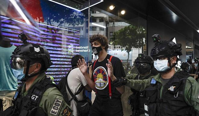 "A man wearing a ""Free Tibet"" T-shirt is surrounded by police during China's National Day in Causeway Bay, Hong Kong on October 1. Photo: AP"