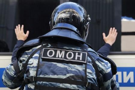 A law enforcement officer detains a man after a rally to demand authorities allow opposition candidates to run in a local election in Moscow