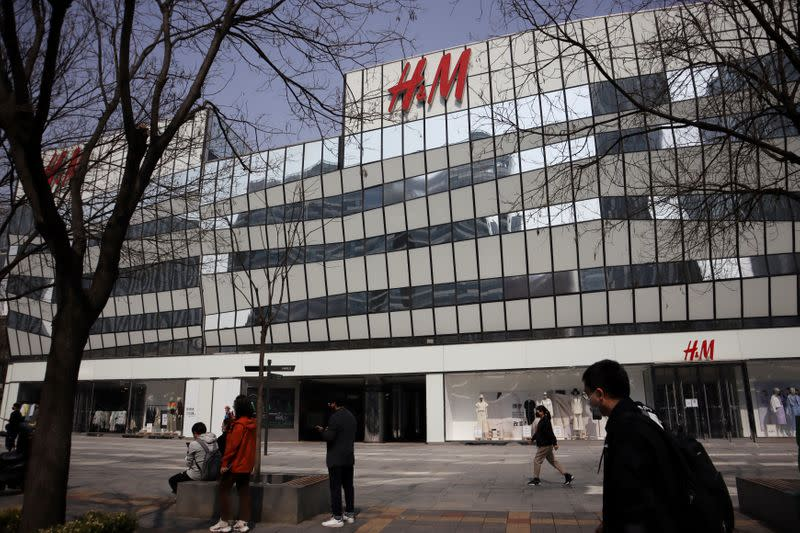 FILE PHOTO: People walk past an H&M store at a shopping complex in Beijing
