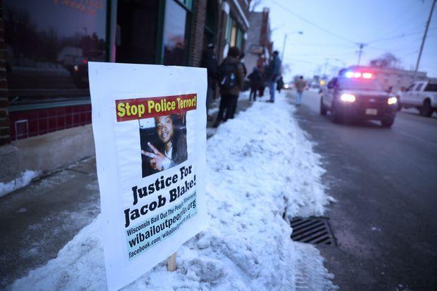 A police car drives past a sign showing support for Jacob Blake Jr., who was shot seven times in the back by a Kenosha police officer on Aug. 23, 2020. Blake was left paralyzed from the waist down. (Photo: Scott Olson/Getty Images)
