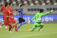 Japan's Takefusa Kubo shoots by China's goalkeeper Junling Yan during a FIFA World Cup qualifying soccer match between China and Japan in Doha, Qatar, Tuesday, Sept. 7, 2021. (AP Photo/Hussein Sayed)