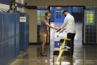 Election judge Tyler Sahnow, left, sprays hand sanitizer to John Enloe as he arrives to vote at Northeast Middle School in Minneapolis, Minnesota, during the first election in Minnesota since the full outbreak of the COVID-19 pandemic, Tuesday, Aug. 11, 2020. (Anthony Souffle/Star Tribune via AP)