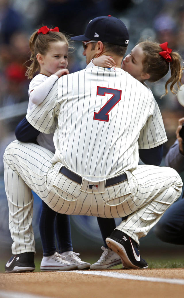 Minnesota Twins' Joe Mauer, the subject of retirement talk, is accompanied at first base by his twin daughters during a baseball game against the Chicago White Sox Sunday, Sept. 30, 2018, in Minneapolis. (AP Photo/Jim Mone)