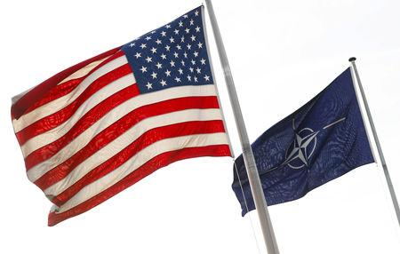 NATO and U.S. flags fly at the entrance of the Alliance's headquarters during a NATO foreign ministers meeting in Brussels