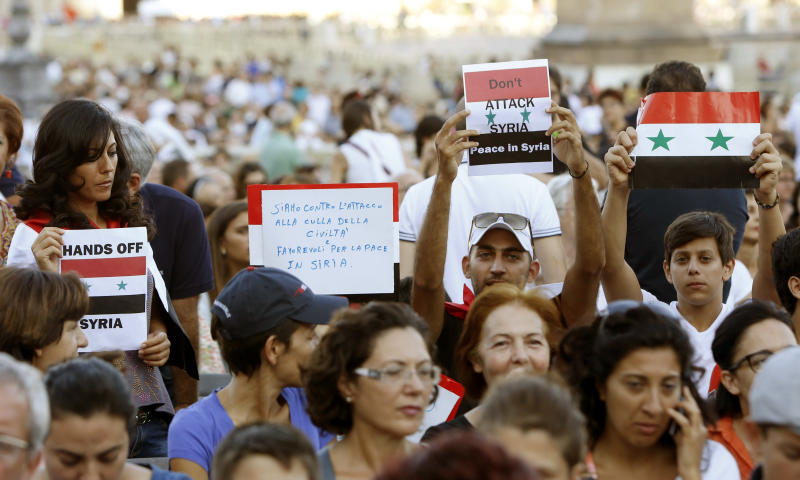 People hold Syrian flags and signs against a possible attack to Syria, prior to the start of a vigil for peace attended by Pope Francis in St. Peter's Square at the Vatican, Saturday, Sept. 7, 2013. Tens of thousands of people have answered Pope Francis' call and massed in St. Peter's Square for a 4-hour-long prayer vigil for peace in Syria. It was believed to be one of the first, and certainly the largest popular rally in the West against U.S.-led plans to strike Syria following the Aug. 21 chemical weapons attack near Damascus. (AP Photo/Riccardo De Luca)