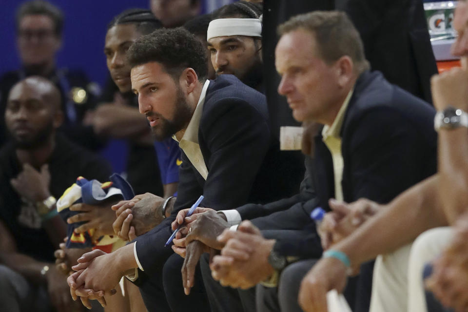 Injured Golden State Warriors guard Klay Thompson, center left, watches from the bench during the second half of an NBA basketball game against the Portland Trail Blazers in San Francisco, Monday, Nov. 4, 2019. (AP Photo/Jeff Chiu)