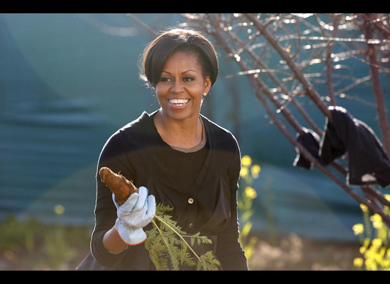 US First Lady Michelle Obama holds up a carrot as she gardens during a community service project at Vhuthilo Community Center in Soweto township, Johannesburg, South Africa, June 22, 2011. AFP PHOTO /Charles Dharapak / POOL (Photo credit should read CHARLES DHARAPAK/AFP/Getty Images)