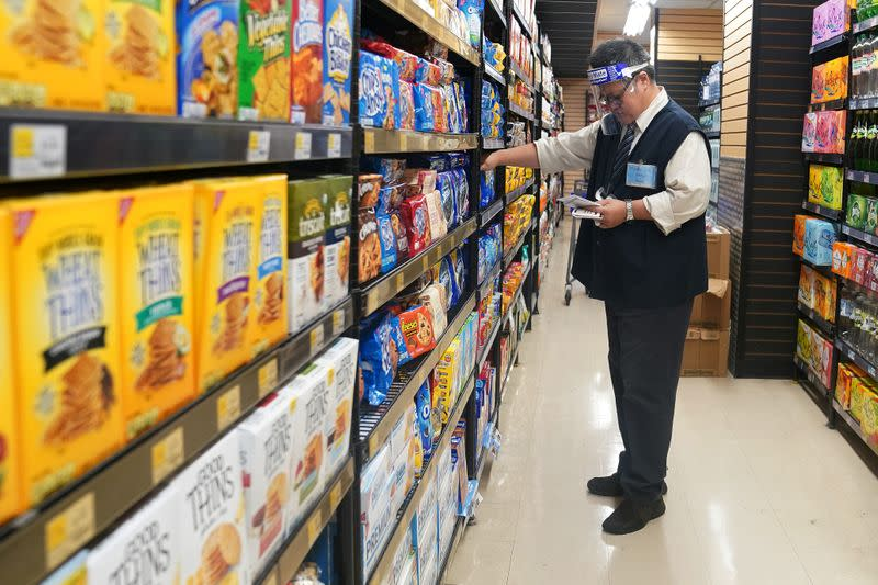 FILE PHOTO: A worker with a face shield checks products on the shelf of a grocery store
