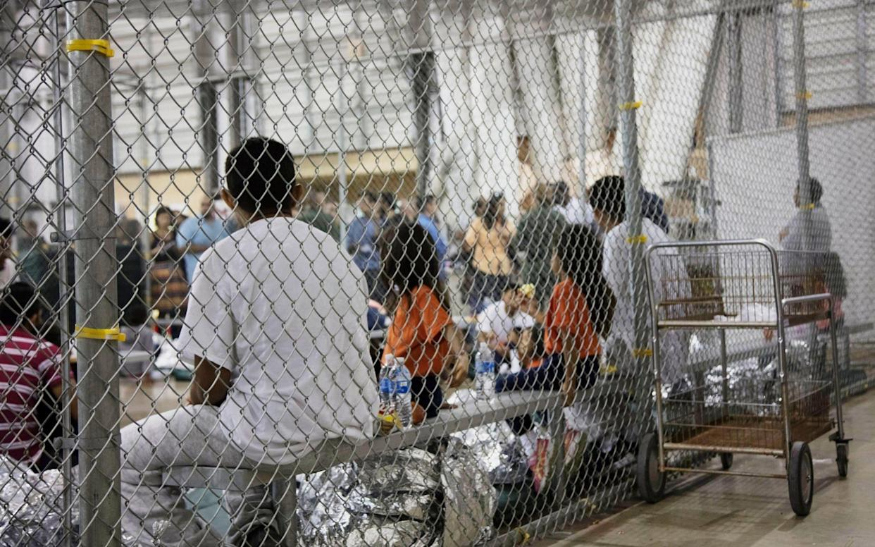 People who've been taken into custody related to cases of illegal entry into the United States, sit in one of the cages at a facility in McAllen, Texas - U.S. Customs and Border Protection's Rio Grande Valley Sector