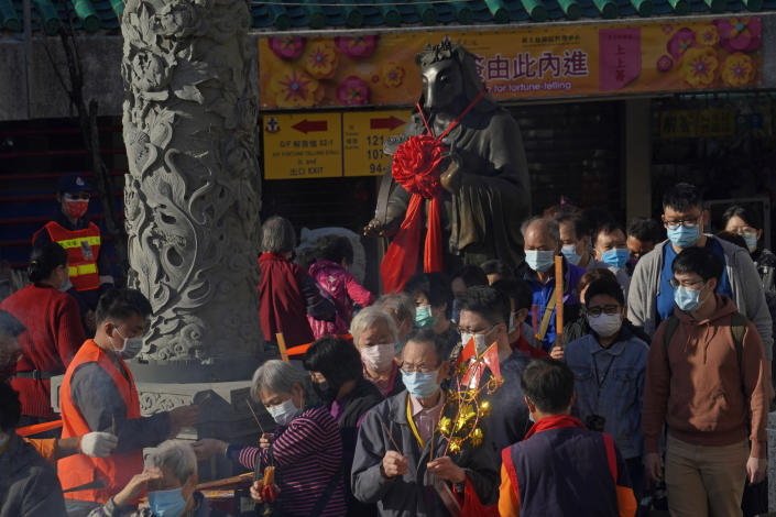 Worshippers wearing face masks to protect against the spread of the coronavirus, queue beside the statue of ox as they pray at the Wong Tai Sin Temple, in Hong Kong, Friday, Feb. 12, 2021 to celebrate the Lunar New Year which marks the Year of the Ox in the Chinese zodiac. (AP Photo/Kin Cheung)