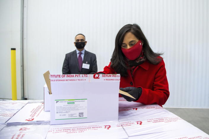 Anita Anand, Canada's Minister of Public Services and Procurement opens a box with some of the first 500,000 of the two million AstraZeneca COVID-19 vaccine doses that Canada has secured through a deal with the Serum Institute of India in partnership with Verity Pharma, Wednesday, March 3, 2021, at a facility in Milton, Ontario. (Carlos Osorio/Pool Photo via AP)
