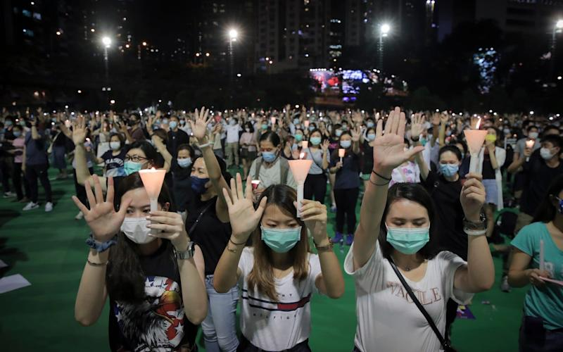 Protesters gather at a vigil for victims of the Tiananmen Square Massacre - AP