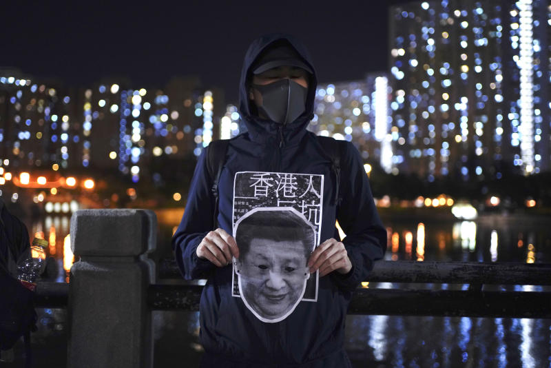 A protester holds a Chinese President Xi Jinping mask during a protest in Hong Kong, Friday, Oct. 18, 2019. Hong Kong pro-democracy protesters are donning cartoon/superhero masks as they formed a human chain across the semiautonomous Chinese city, in defiance of a government ban on face coverings. (AP Photo/Vincent You)