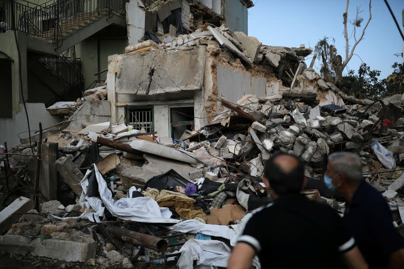 Locals look at a destroyed house where the wife and two of the daughters of Syrian refugee Ahmed Staifi were killed following a massive explosion, in Beirut