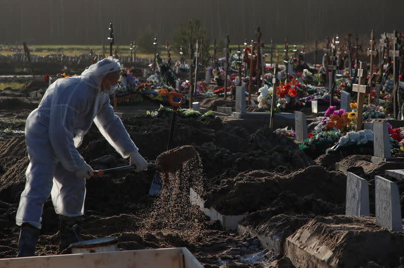 A grave digger buries a person at a graveyard in Saint Petersburg