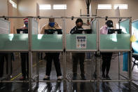FILE - In this Nov. 3, 2020, file photo, people vote at a polling place on Election Day in Las Vegas. Months of discussions about racial justice are being followed by change at the ballot box. (AP Photo/John Locher, File)