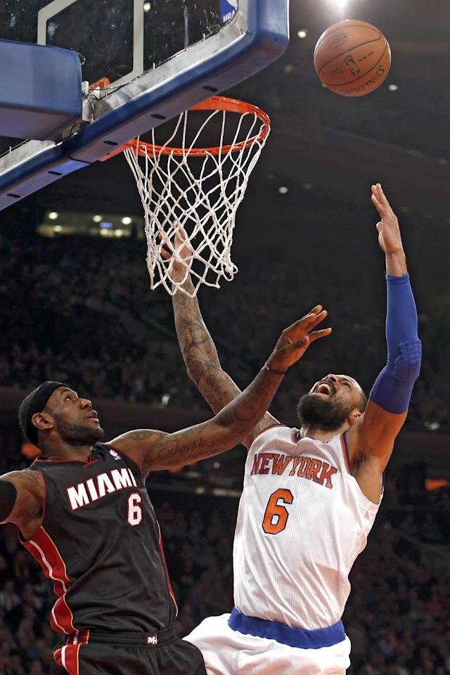 Miami Heat's LeBron James, left, fouls New York Knicks' Tyson Chandler, right, as they fight for a rebound during the first half of an NBA basketball game Saturday, Feb. 1, 2014, in New York. (AP Photo/Jason DeCrow)