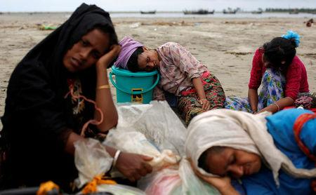 Exhausted Rohingya refugees rest on the shore after crossing the Bangladesh-Myanmar border by boat through the Bay of Bengal in Shah Porir Dwip, Bangladesh, September 10, 2017. REUTERS/Danish Siddiqui