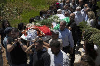 Palestinian mourners carry the body of Suha Jarrar, 30-year-old, daughter of Khalida Jarrar who is a prisoner in an Israeli jail, during her funeral, in the West Bank city of Ramallah, Tuesday, July 13, 2021. Khalida Jarrar, 58, a leading member of the Popular Front for the Liberation of Palestine, has been in and out of Israeli prison in recent years. Palestinian activists and human rights groups urged Israel to allow Jarrar to attend her daughter's funeral. (AP Photo/Majdi Mohammed)