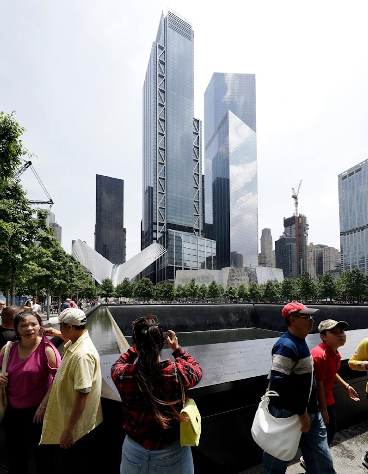 In this June 8, 2018 photo, 3 World Trade Center towers above visitors at the September 11 Memorial in New York. The center's latest skyscraper opens Monday. (AP Photo/Mark Lennihan)