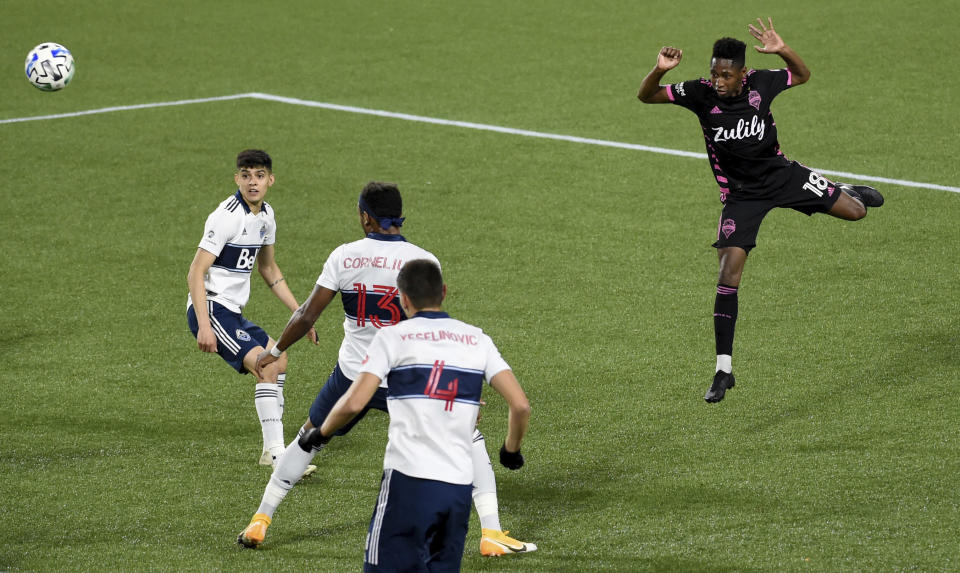 Seattle Sounders defender Kelvin Leerdam right puts a shot on goal as Vancouver Whitecaps defender Cristian Gutierrez, left, watches during the first half of an MLS soccer match in Portland, Ore., Tuesday, Oct. 27, 2020. (AP Photo/Steve Dykes)