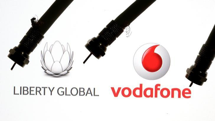Coaxial TV Cables are seen in front of Vodafone and Liberty Global logos in this illustration