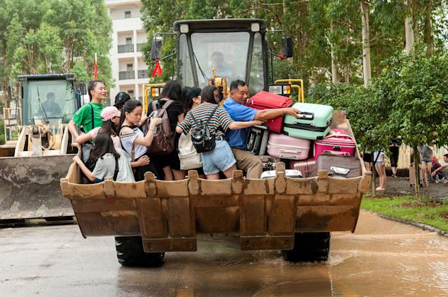 <p>Students are transferred by a forklift through a flooded area at a college in Guilin, Guangxi province, China, July 3, 2017. (Photo: Stringer/Reuters) </p>