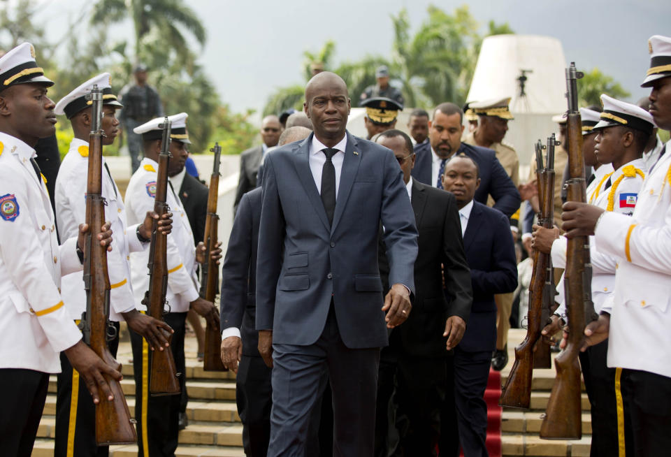 FILE - In this April 7, 2018, file photo, Haiti's President Jovenel Moise, center, leaves the museum during a ceremony marking the 215th anniversary of revolutionary hero Toussaint Louverture's death, at the National Pantheon museum in Port-au-Prince, Haiti. Moïse was assassinated after a group of unidentified people attacked his private residence, the country's interim prime minister said in a statement Wednesday, July 7, 2021. (AP Photo/Dieu Nalio Chery, File)