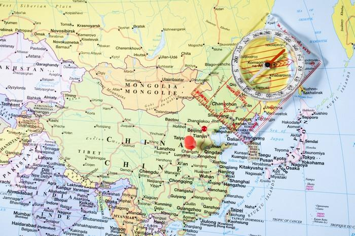 A plastic compass lies on a map of China.