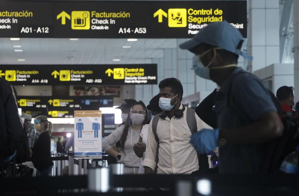 Passengers stand in the check-in area of Tocumen International Airport for a departing flight in Panama City, Monday, Oct. 12, 2020. Panama is lifting a broad spectrum of COVID-19 pandemic-related restrictions on Monday, including re-opening international flights and allowing hotels, casinos, and tourism-related activities. (AP Photo/Arnulfo Franco)