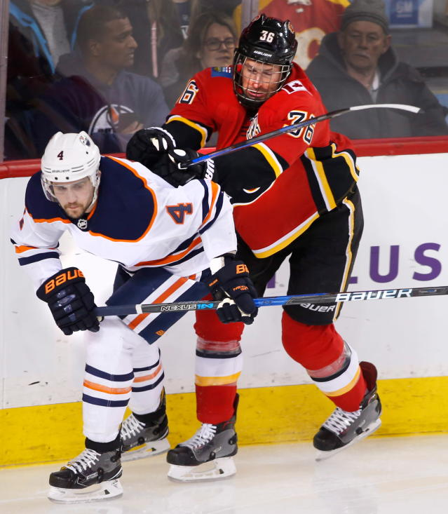 Edmonton Oilers' Kris Russell (4) takes a push from Calgary Flames' Troy Brouwer (36) during first period NHL hockey action in Calgary, Alberta, Saturday, March 31, 2018. (Larry MacDougal/The Canadian Press via AP)
