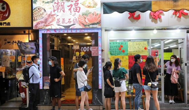 Diners line up outside Kwong Wing Catering in Hong Kong's Tsim Sha Tsui district on the first night evening dining has been allowed in nearly six weeks. Photo: K. Y. Cheng