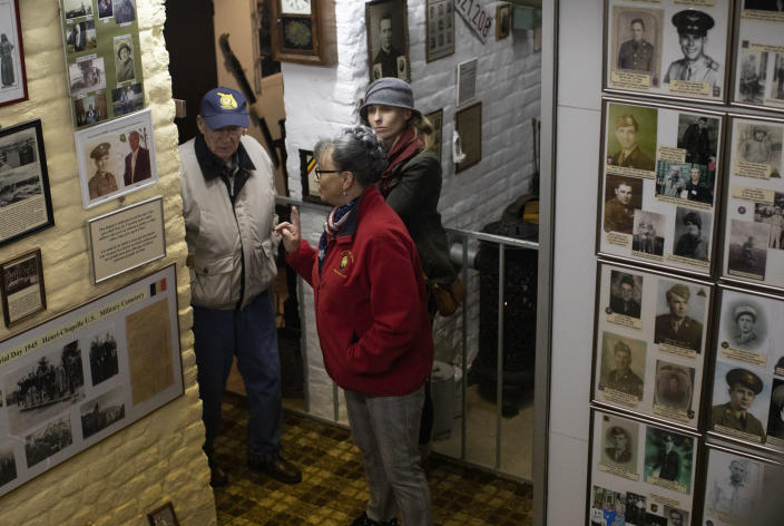 In this photo taken on Tuesday, Dec. 10, 2019, Mathilde Schmetz takes U.S. Battle of the Bulge veteran Arthur Jacobson, left, through the Remember Museum 39-45 in Thimister-Clermont, Belgium. In the bucolic, verdant hills which were once among the worst killing grounds of WWII Marcel and Mathilde Schmetz have shared coffee and cake with countless veterans, telling stories that span generations. Veterans of the WWII Battle of the Bulge are heading back to mark, perhaps the greatest battle in U.S. military history, when 75-years ago Hitler launched a desperate attack deep through the front lines in Belgium and Luxembourg to be thwarted by U.S. forces. (AP Photo/Virginia Mayo)