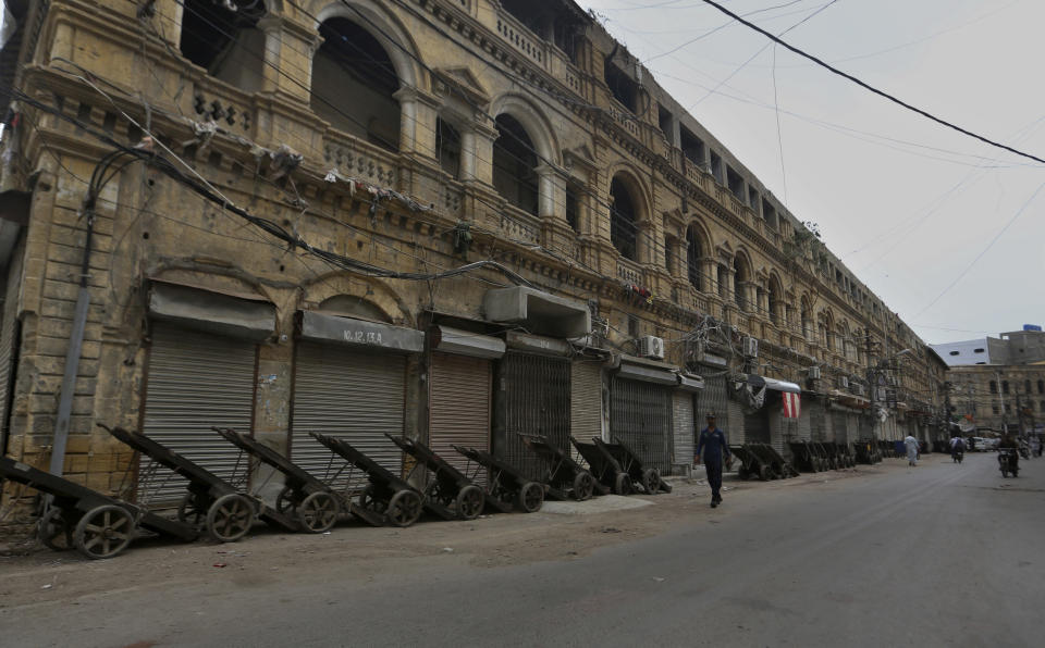 A private security guard walks through a market closed due to new restrictions announced by provincial government to help control the spread of the coronavirus, in Karachi, Pakistan, Friday, July 30, 2021. (AP Photo/Fareed Khan)