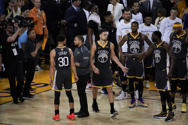 Golden State Warriors guard Klay Thompson (11) is greeted by teammates after walking back onto the court to shoot free throws after an injury against the Toronto Raptors during the second half of Game 6 of basketball's NBA Finals in Oakland, Calif., Thursday, June 13, 2019. (AP Photo/Tony Avelar)