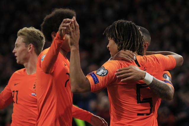 Netherlands players hug Netherlands' Nathan Ake, right, after he scored his side's second goal during the Euro 2020 group C qualifying soccer match between The Netherlands and Estonia at the Johan Cruyff ArenA in Amsterdam, Netherlands, Tuesday, Nov. 19, 2019. (AP Photo/Peter Dejong)