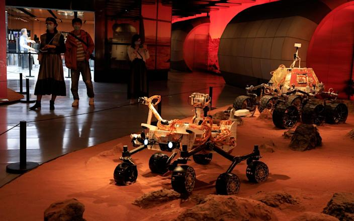 Visitors admire an exhibition depicting rovers on Mars in Beijing - AP Photo/Ng Han Guan