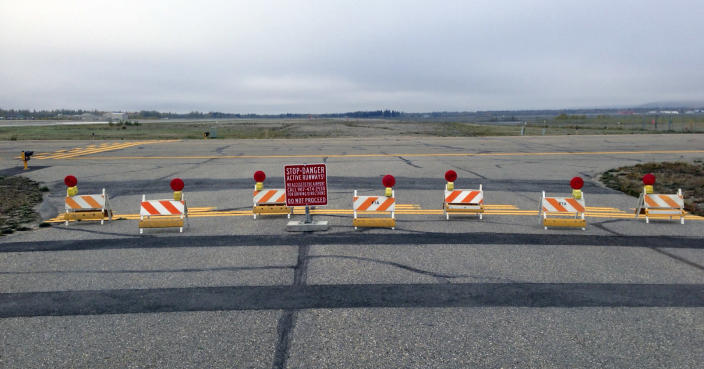 This Sept. 20, 2013 image provided by the Fairbanks International Airport shows the barricaded entrance to a taxiway, at the entrance to Float Pond Road blocking access to Taxiway B in fairbanks, Alaska. A glitch in the Apple Maps app on newer iPhones and iPads guides people up to this runway at Fairbanks International Airport instead of the proper route to the terminal. (AP Photo/Fairbanks International Airport)
