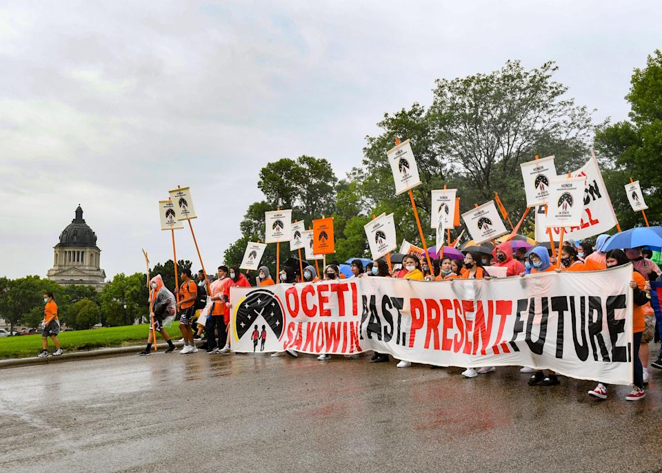 NDN Collective leads a demonstration past the South Dakota capitol building after the final draft of the state's proposed social studies standards left out multiple specific references to the Oceti Sakowin on Monday, September 13, 2021.